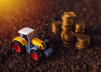 Agricultural tractor toy and golden coins on fertile soil land, income from activity in agriculture or investment and bank loans for farm development